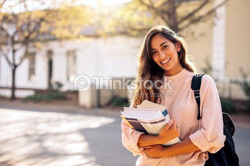 female college student with books outdoors stock photo thinkstock