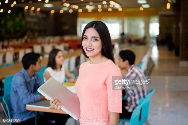 Female college student with laptop smiling at camera