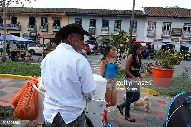 Female Colombian teenagers pass by a street vendor on a Sunday in the main town square on January 24 2016 in Filandia Colombia Filandia is a town and...