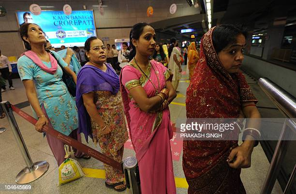 Female commuters queue to board a womenonly coach at a Delhi Metro train station in New Delhi on October 2 2010 The Indian capital is scheduled to...