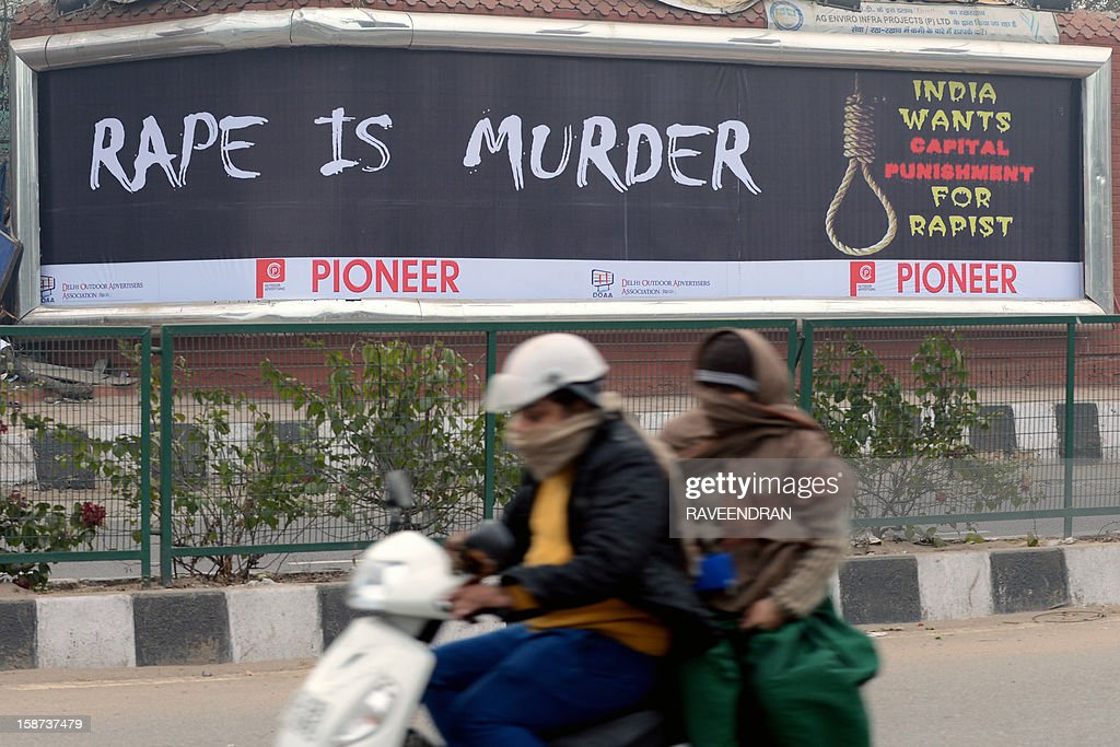 Female commuters ride a scooter past a billboard, calling for capital punishment against rape, in New Delhi on December 27, 2012. An Indian student who was left fighting for her life after being brutally gang raped on a bus in New Delhi arrived December 27 in Singapore for treatment at a leading hospital. The attack sparked a wave of protests across India in which a policeman died and more than 100 police and protestors were injured.