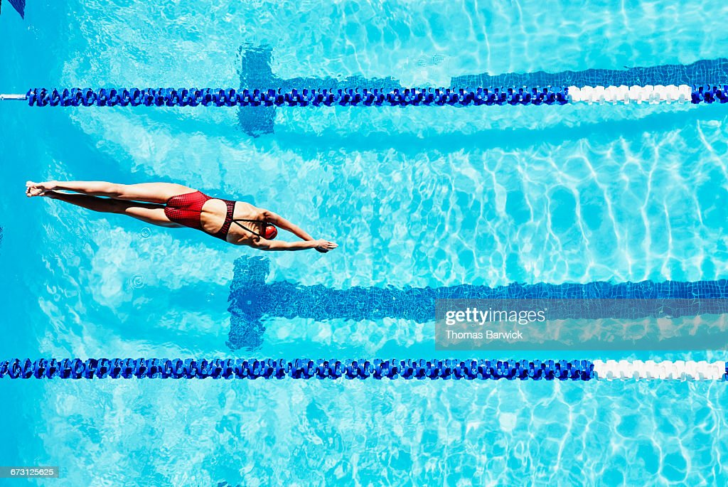 Female competitive swimmer diving into pool