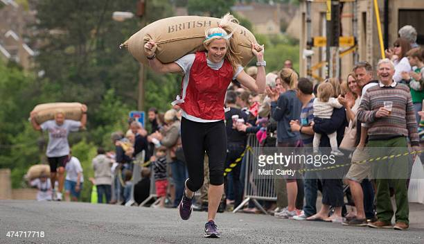 Female competitors race carrying woolsacks up the steep Gumstool Hill in the centre of Tetbury on May 25 2015 in Gloucestershire England The race...