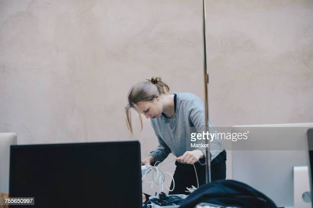 Female computer programmer fixing tangled cables against wall in office