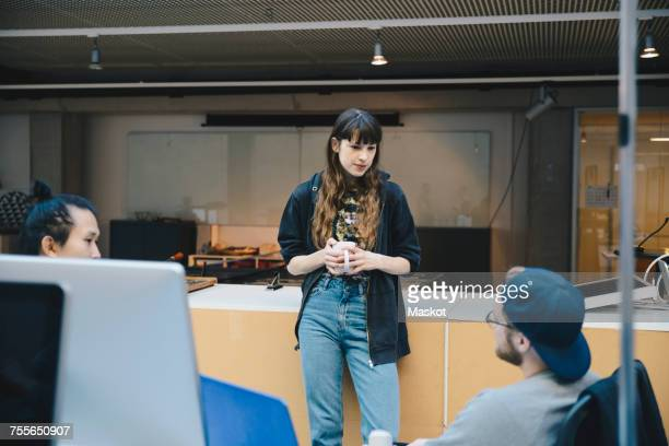 Female computer programmer holding coffee mug while discussing with colleagues in office