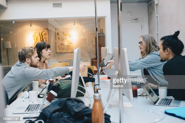 Female computer programmer showing digital tablet to colleagues at desk in office