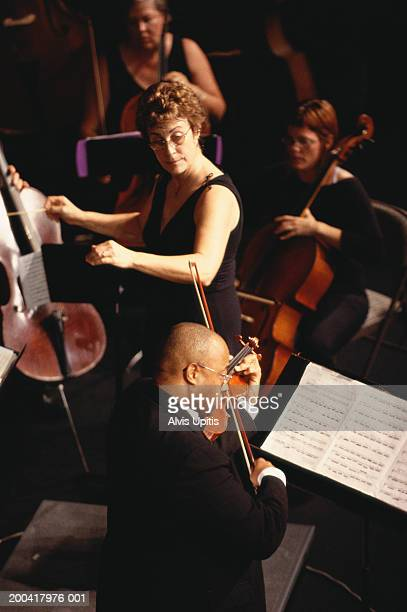 Female conductor and male violin soloist performing in orchestra
