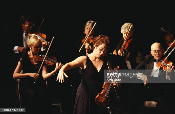 Female conductor and violin section performing in orchestra