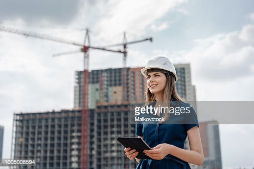 Female construction engineer. Architect with a tablet computer at a construction site. Young Woman looking, building site place on background. Construction concept : Stock Photo