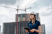 Female construction engineer. Architect with a tablet computer at a construction site. Young Woman look in camera, building site place background.