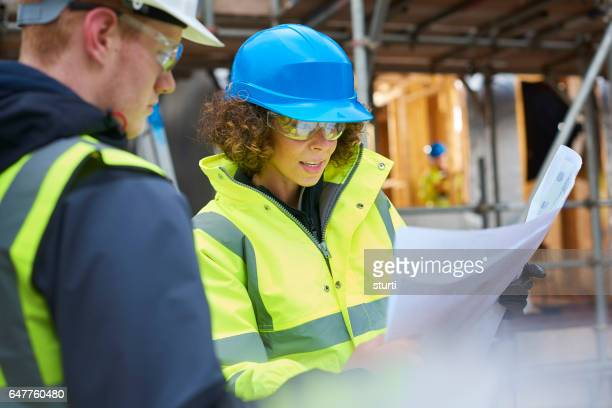female construction foreman instructing a worker .