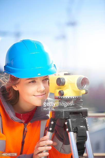 female construction site surveyor looking through theodolite