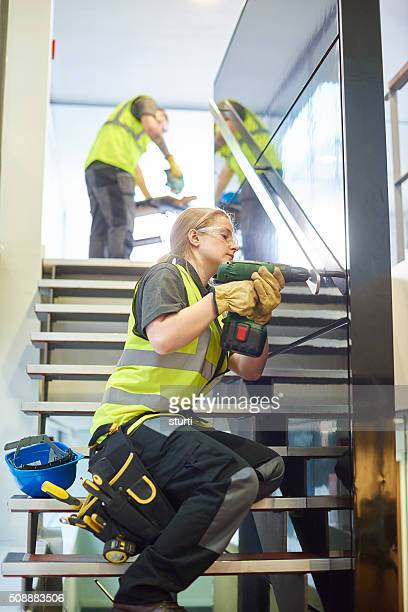 female construction worker fitting handrails