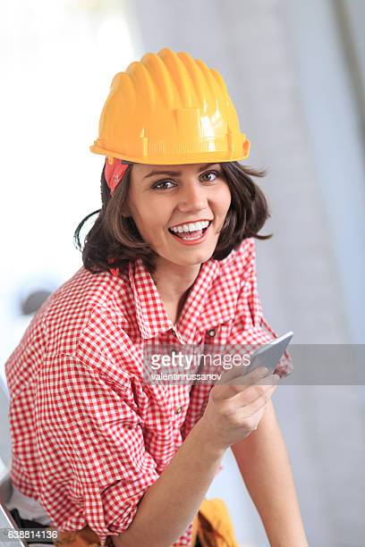 Female construction worker holding smart phone