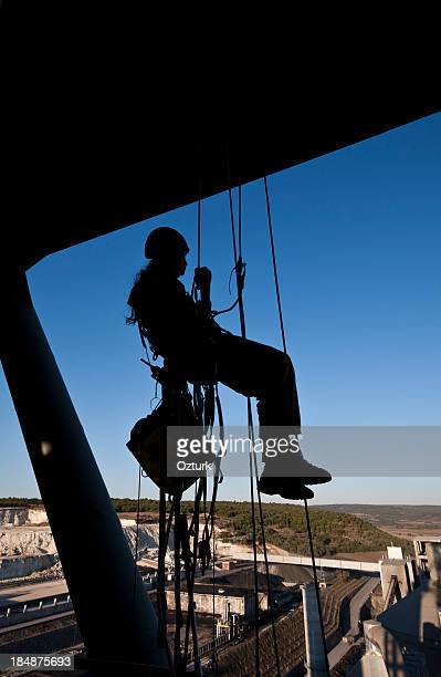 Female construction worker on ropes and pulleys high above