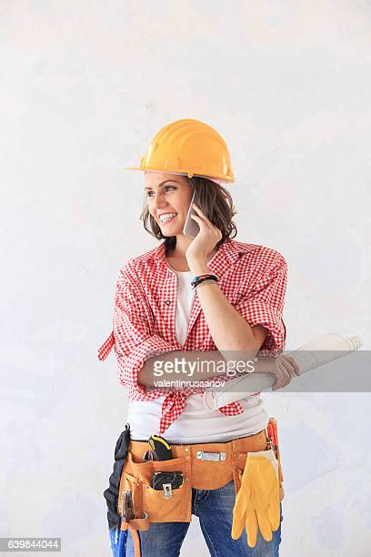 Female construction worker talking on smart phone