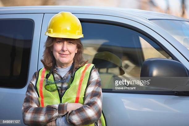 Female Construction Working Standing by Minivan