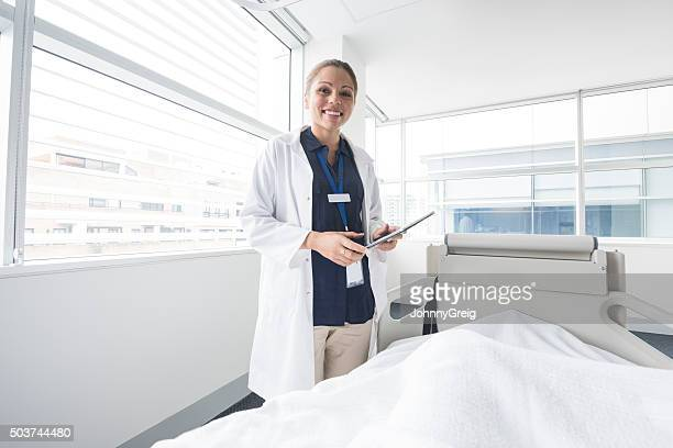 Female consultant in hospital ward with digital tablet