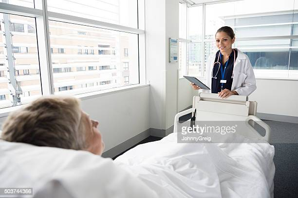 Female consultant talking to mature woman in hospital