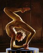 Female contortionist bending over backwards, profile