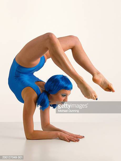 Female contortionist with blue hair, balancing on floor
