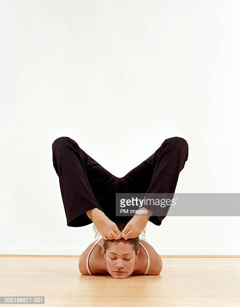 Female contortionist with feet on head, eyes closed