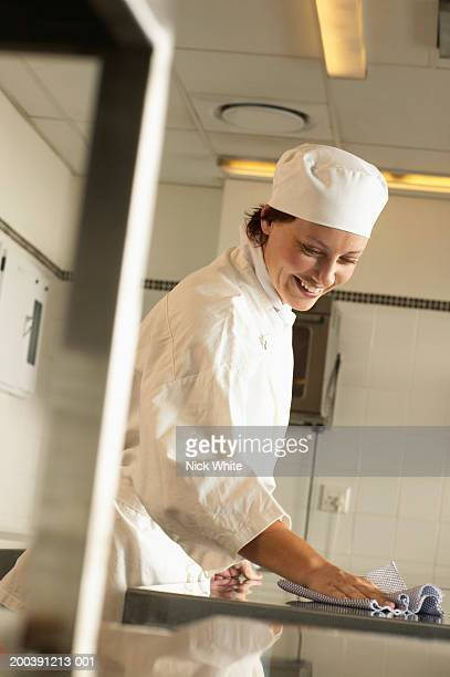 Female cook cleaning kitchen worktop, smiling