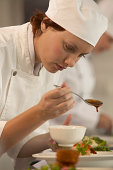 Female cook pouring dressing on salad, close-up (focus on cook)