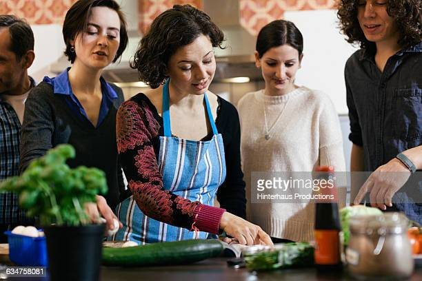 Female cook surrounded by students in cooking clas