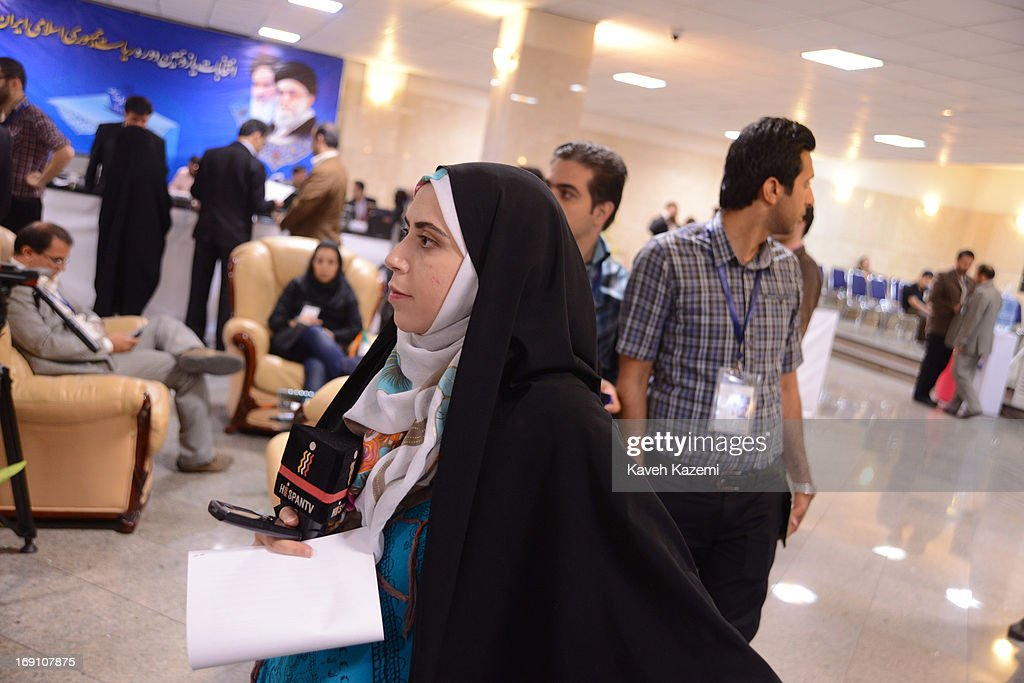 A female correspondent working for HispanTV in a black chador holds a microphone with the TV logo on it while observing the candidates enrolling for presidential election in the registration hall of the Ministry of Interior on May 10, 2013 in Tehran, Iran. HispanTV is a Spanish language television channel operated by IRIB, Iran's state-owned public broadcasting corporation. It began broadcasting in December 2011 being the very first Spanish-language TV network in the Middle East.