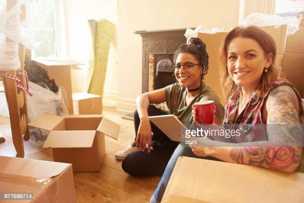 female couple smile to camera in their new home