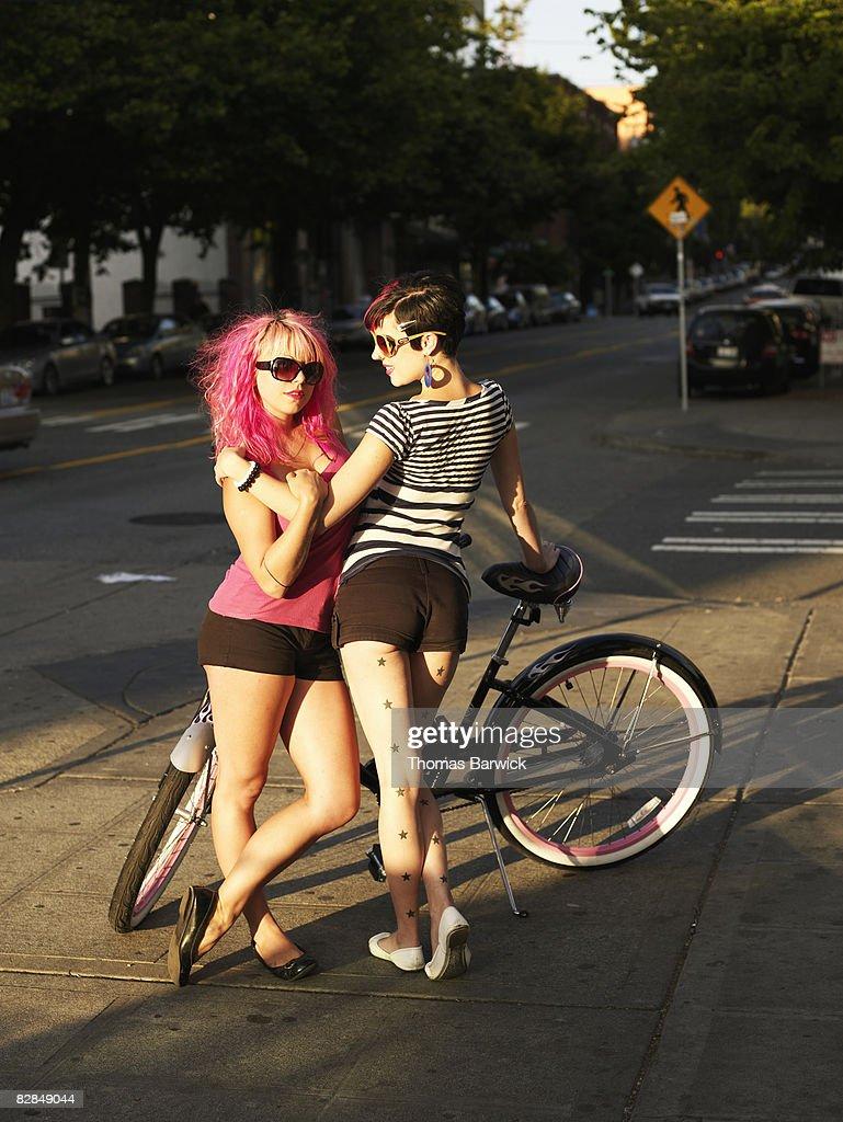 Female couple standing on sidewalk with bike, embracing