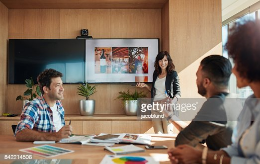 Female coworker making presentation in office : Stock Photo