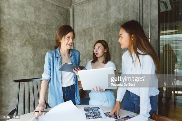 Female coworkers discussing a project in a new office space