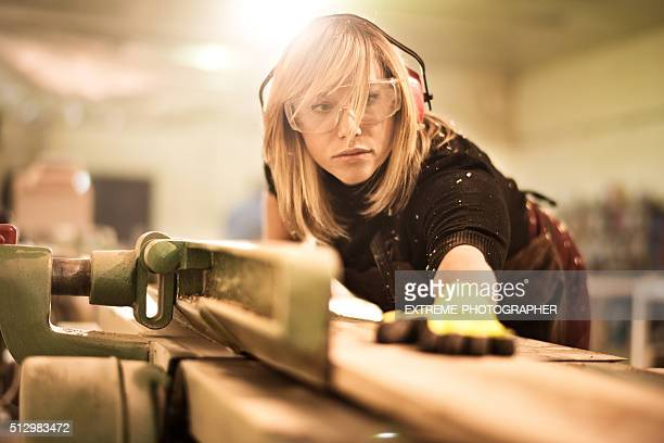 Female craftsperson working with plank