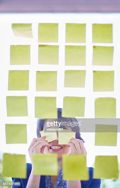 Female creative professional behind glass pane with adhesive notes covering her eyes