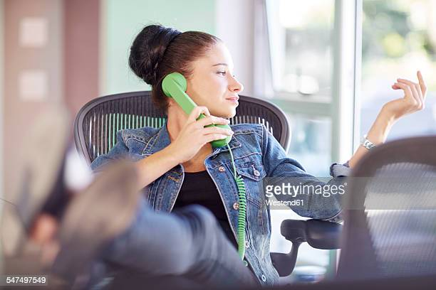 Female creative professional telephoning with feet up in the office