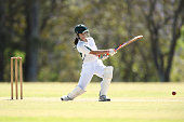 A young girl plays a shot while batting in a game of cricket