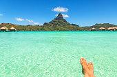 Female crossed legs over tropical blue lagoon and Otemanu mount, Bora Bora, near Tahiti, in French Polynesia.