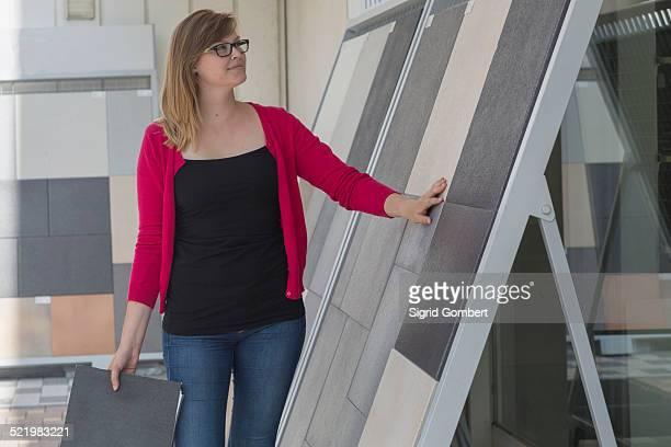 Female customer admiring floor tile display in hardware store