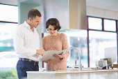 Female customer and salesman looking at brochure in kitchen showroom
