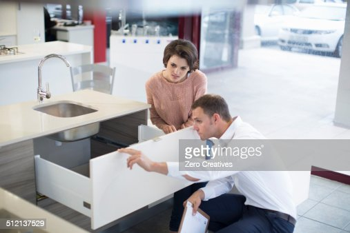 Female customer and salesman looking at drawer in kitchen showroom