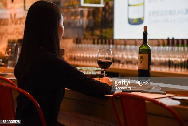 A female customer enjoys a glass of wine at Chateau Mercian Tokyo Guest Bar in Tokyo Japan on Monday Feb 6 2017 Sake made from fermented rice is the...