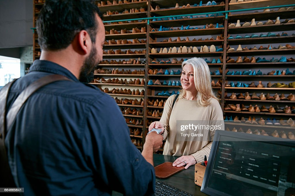 Female customer handing credit card to cobbler in traditional shoe shop