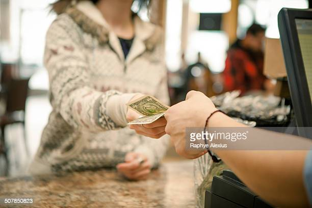 Female customer handing payment to waiter over cafe counter