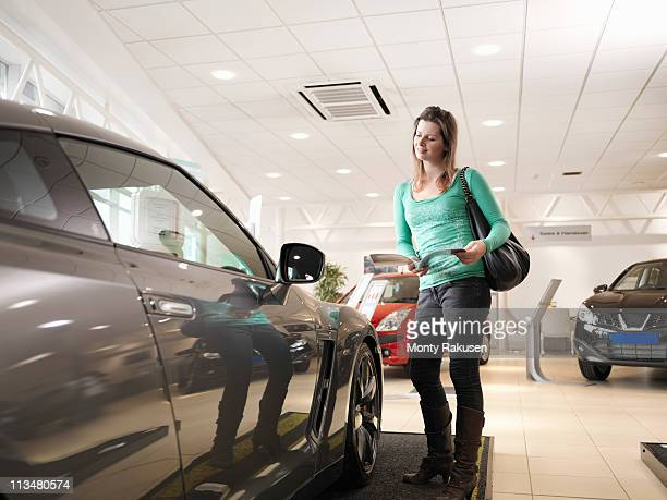 Female customer holding a brochure looking at car in car showroom