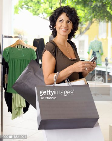Female customer holding shopping bags and mobile phone : Stock Photo