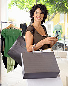 Female customer holding shopping bags and mobile phone