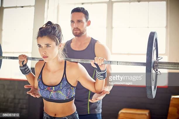 Female customer lifting barbell while coach assisting her in gym