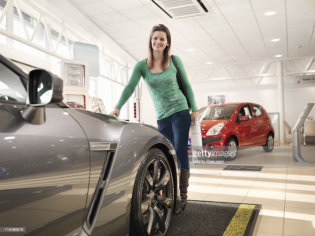 Female customer looks at car in car dealership, touching car